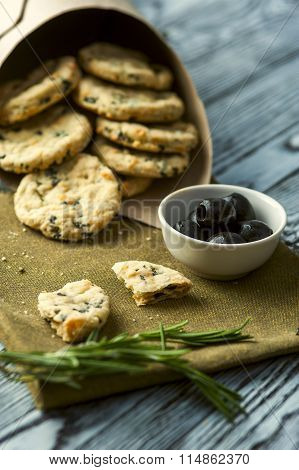 Cookies with cheese, olives and rosemary on