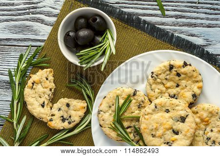 Cookies with cheese, olives and rosemary on napkin