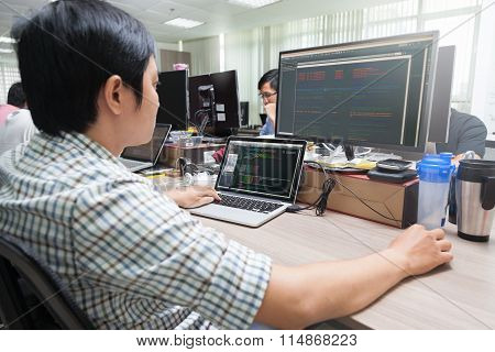 Asian Developer Using Laptop Computer Sitting Working