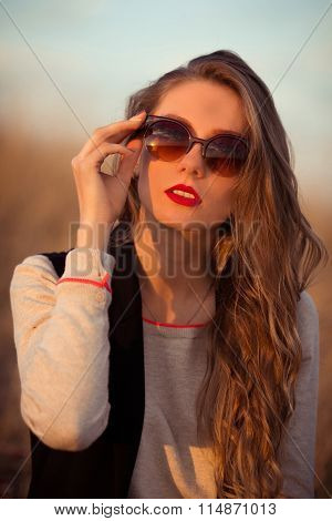 Sunny, happy, brunette, glamour girl with wearing sunglasses, corrects, holds modern, new, stylish, brown, sunglasses. Woman, good, taste. Sunset. Summer time. Glamour Sunglasses. Original sunglasses. Trend, excellent