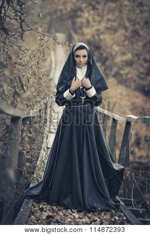 One pretty, sexy nun, cute nun, peaceful nun, alone, posing nun, attractive nun, young nun, holy nun, sister with a cross outdoors, forest, old, wooden suspension bridge with frightening view, special uniform, veil