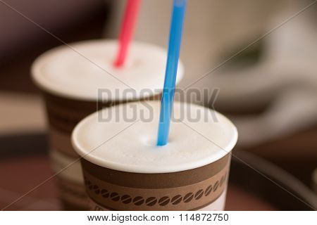 Two Paper Cups Of Cappuccino With Straw