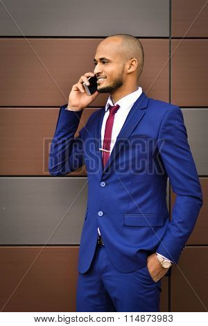African important, young, successful, smiling businessman speaks on cell phone, gives very important, necessary advice, leaning on the wealth of experience, office, close up, leader, style, forbes, executive, boss.