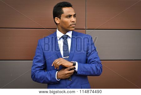 African important,handsome,young person,happy businessman,worker corrects hours on his arm,looks for job or reached career top,stands near the main office.His official style is perfect,face is serious