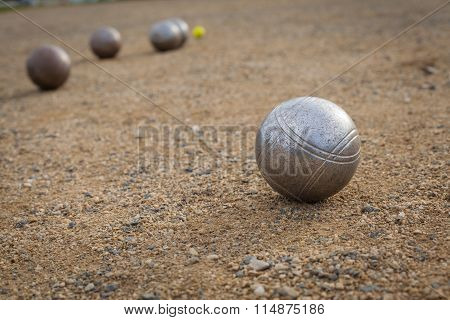 Petanque Balls On A Sandy Pitch With Other Metal Ball In The Background