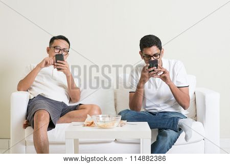Friends sitting on sofa and playing on their phones at home.