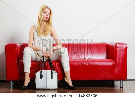 Fashionable Girl With Bag Handbag On Red Couch