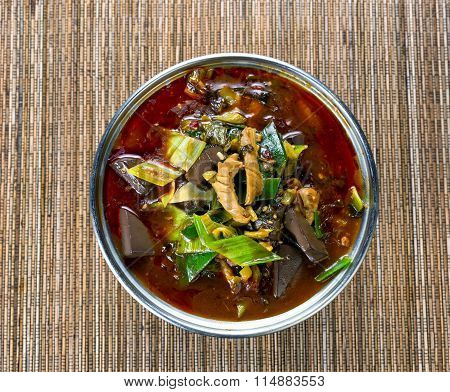 Freshly Cooked Spicy Vegetable Soup In Pot On Bamboo Mat Background