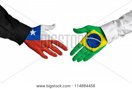 Chile and Brazil leaders shaking hands on a deal agreement