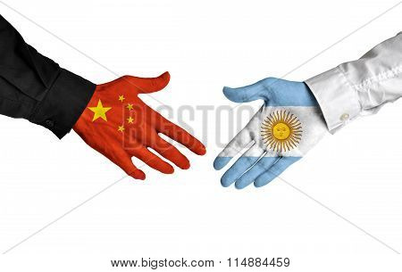 China and Argentina leaders shaking hands on a deal agreement