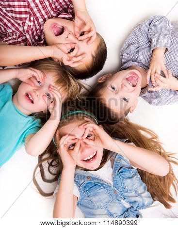 children lying on the floor with hands imitating glasses