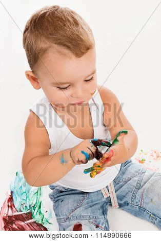 cute little boy painting his hands