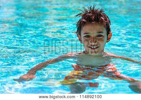 Boy kid child eight years old inside swimming pool portrait happy fun bright day
