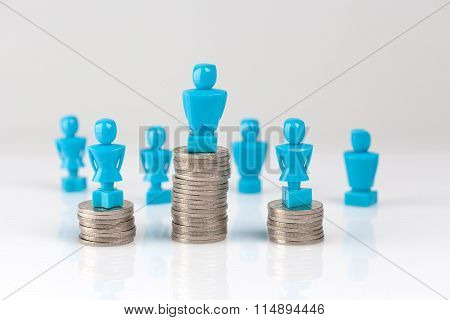 Male And Female Figurines Standing On Top Of Coin Piles