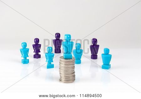 Male Figurine Placed On Top Of Coins Pile With More Figurines In The Background.