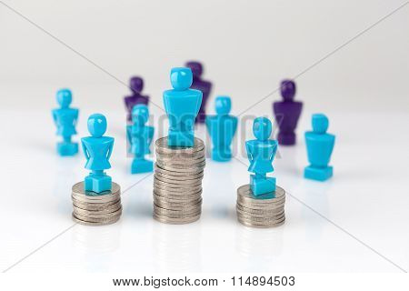 Male And Female Figurines Standing On Top Of Coin Piles With Other Figurines In The Background.