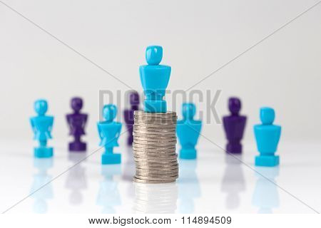 Male Figurine Placed On Top Of Pile Of Coins With Additional Figurines In The Background