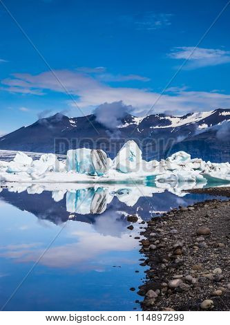 Ocean Bay is surrounded by volcanic mountains and glaciers. Icebergs and ice floes are reflected in the mirrored water. Ice lagoon in Iceland