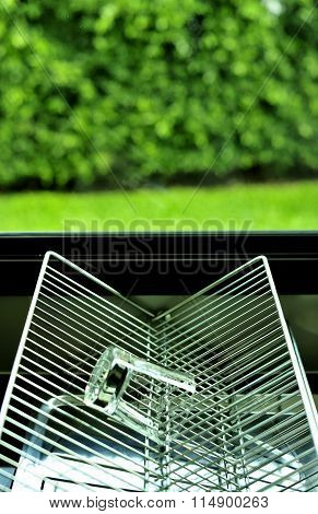 Outside the kitchen window, grille, glass upside down.