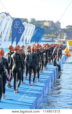 Large Group Of Female Triathletes Wearing Black Swimsuit Waiting For The Start