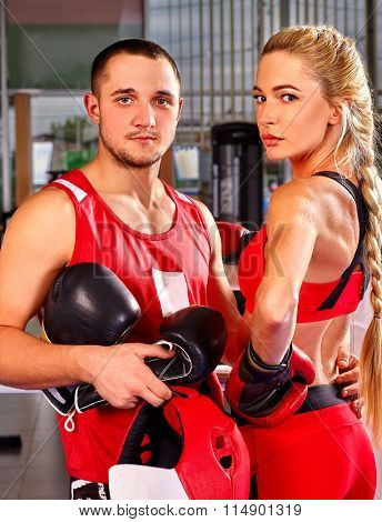 Female boxer with your male coach after workout in gym looking at camera.