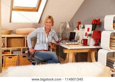 Happy woman holding phone, sitting in study at home, looking away.