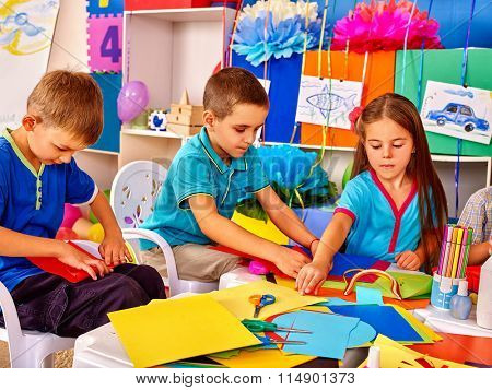Group kids of three people making colored paper on table in kindergarten .