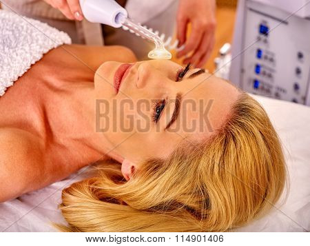 Young beautiful woman looking up receiving electric darsonval facial massage after procedure at beauty salon.