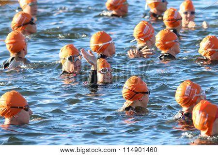 Waving Triathlete Wearing Orange Bathing Caps In The Water