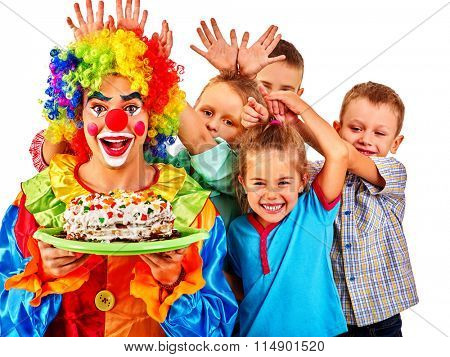 Clown on foreground holding cake on birthday with group children. Isolated.