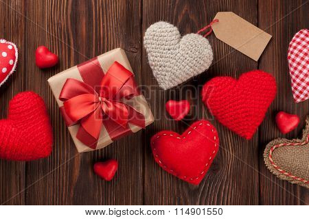Valentines day hearts, candies and gift box over wooden background. Top view