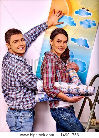 Happy husband and wife glues wallpaper at home.