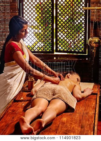 Indian woman do ayurvedic massage with pouch of rice. Passage to India.