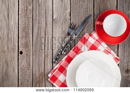 Empty plate and silverware on wooden table. Top view with copy space