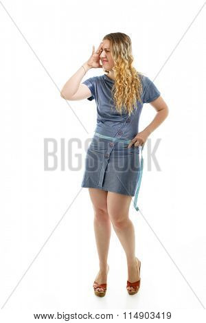 Overweight unhappy young woman measuring her belly over white background