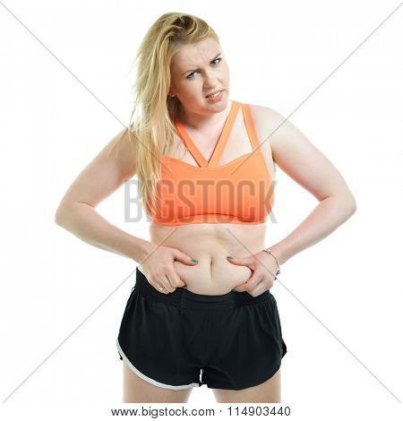 Overweight unhappy young woman showing fat on her belly over white background. Fat, overweight, healthy and unhealthy lifestyle, unhealthy eating, sport, diet concept.