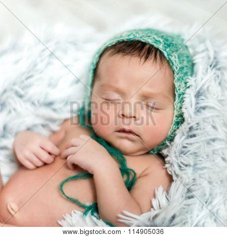 newborn boy with green hat sleeping on grey blanket