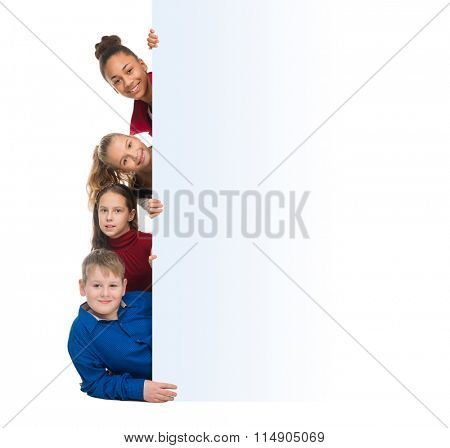 smiling teenagers peeking out from behind an empty blank isolated on white background