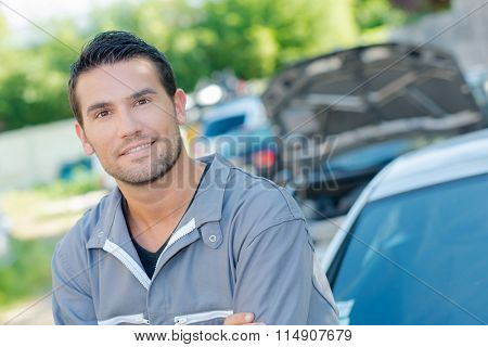 Mechanic wearing overalls stood by a car