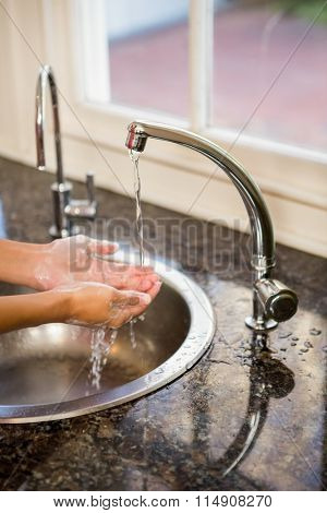 Mid section of woman washing hands in the kitchen
