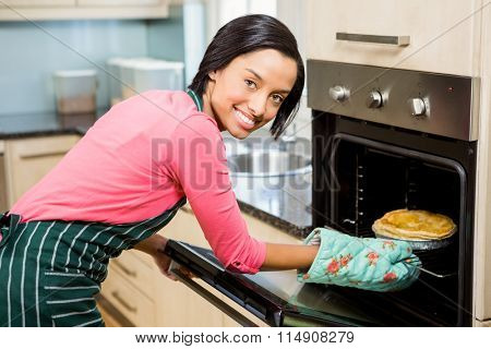 Smiling woman baking pie at home