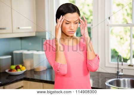 Frowning brunette with hands on face in the kichen