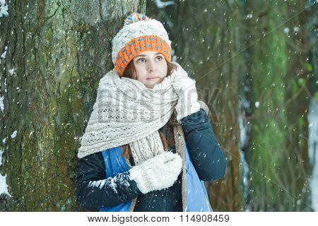 Portrait of romantic girl watching on falling snowflakes wearing knitted hat and bulky scarf in wint