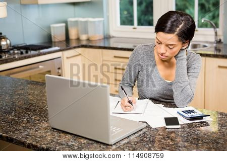 Worried brunette counting bills in the kitchen