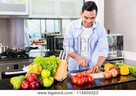 Asian man cutting vegetables in domestic kitchen preparing salad