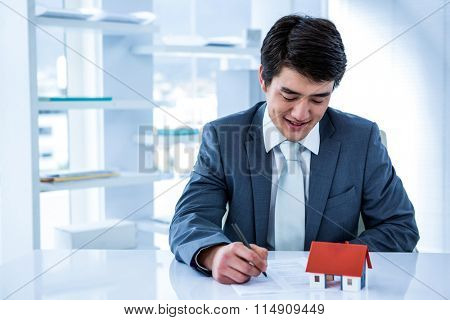 Smiling asian businessman read a estate contract in his office