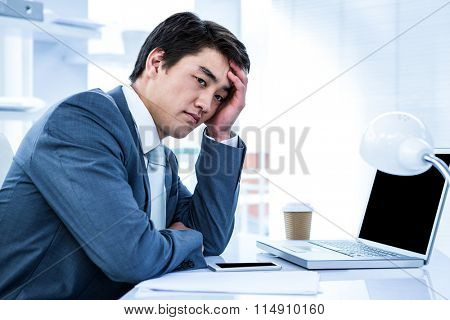 Tired businessman holding his head in his office