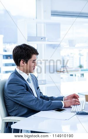 Serious businessman using his computer in his office