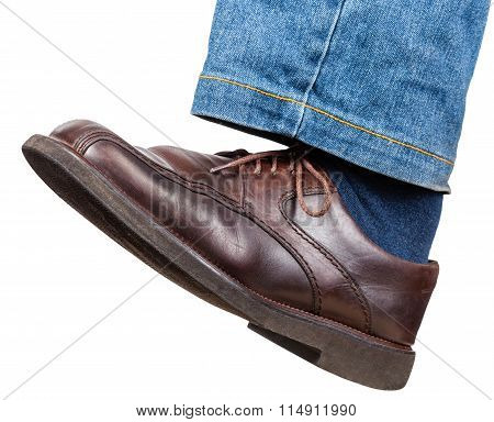 Left Leg In Jeans And Brown Shoe Takes A Step