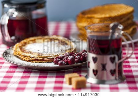 Pancakes with cherries and sugar powder